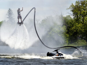 A man is suspended in the air by a water jet hoverboard