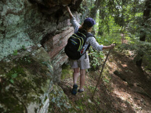 A woman stablizes herself with one hand as she hikes near a rock ledge
