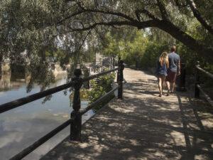 A couple walks along a waterside boardwalk in Lindsay