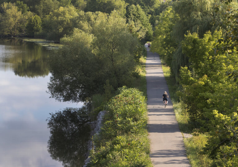 Seen from above, a person runs down a waterside trail