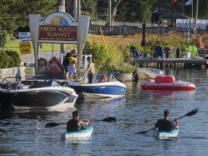 Kayakers paddle through Coboconk, past the Freshwater Summit sign