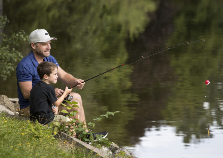 A man and a young boy sit on a grassy bank fishing
