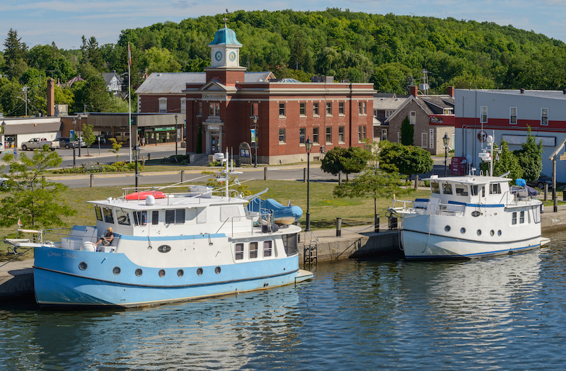 Two boats docked along the Trent-Severn Waterway in Campbellford, with an historic brick building seen in the background