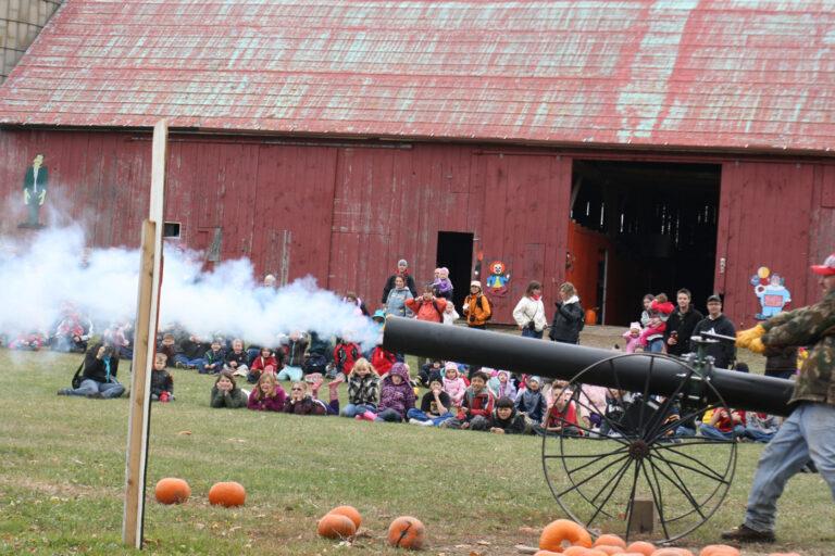 A crowd watches as a man fires a pumpkin cannon