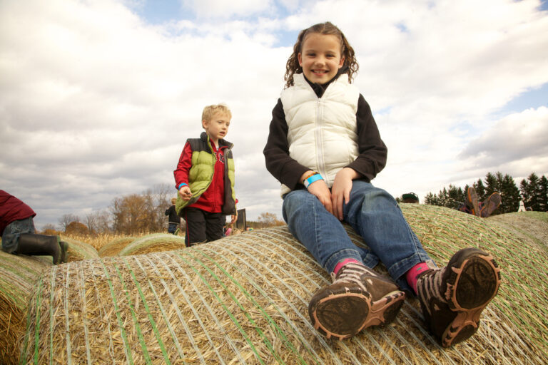 Two kids pose on hay bales at Buckhorn Berry Farm