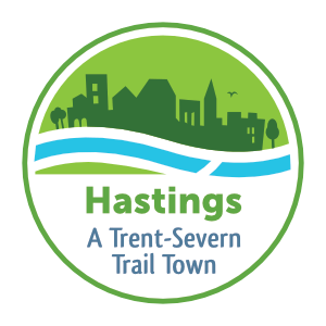 """Logo with town silhouette against flowing water that reads """"Hastings: A Trent-Severn Trail Town"""""""
