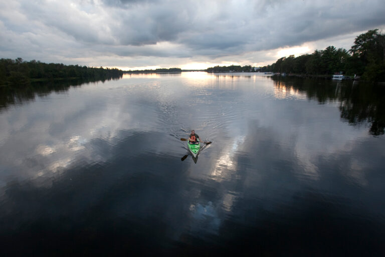 A kayaker is perfectly centred in still waters
