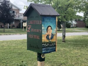 "A little free library box with a portrait of Margaret Laurence ""Lakefield Literary Festival"" painted on the side"