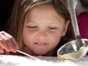 A child looks on expectantly as maple syrup is poured over snow