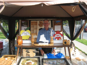 A vendor at the Hastings Farmers Market stands at his booth smiling