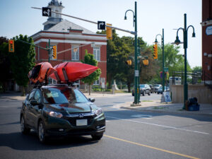 A car with two kayaks on its roof passes through downtown Lakefield