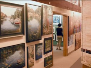 A series of landscape paintings are hang on a wall in the foreground, while a woman browses in another gallery room in the background
