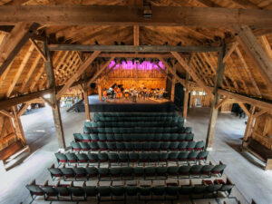 The interior of Westben's timber-frame barn, with the seats unoccupied but a band on stage in the background
