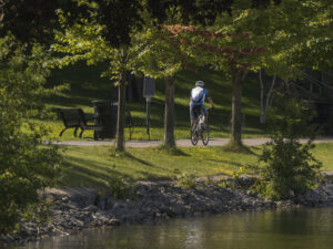 A cyclist rides down a wide path with greenery on his left and water on his right