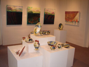 A colourful ceramics display sits in the foreground with impressionistic landscape paintings in the background at Colborne Street Gallery