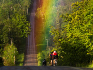 Cyclists descend a hill on a backroad while a rainbow arcs above them