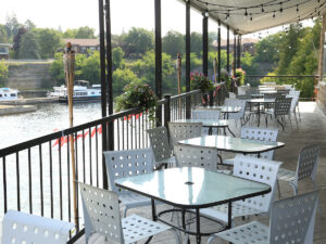 A row of empty tables on a second-storey patio in Fenelon Falls, with the water seen indistinctly in the background