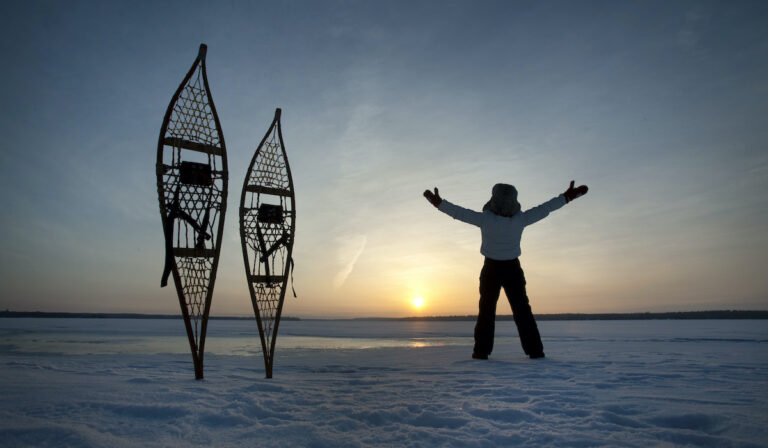 A pair of snowshoes is propped up in the snow while a snowshoer stands with their arms spread to the sunset over an icy lake