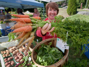 A woman holds a bunch of carrots out towards the camera, while other fresh produce can be seen on the table below
