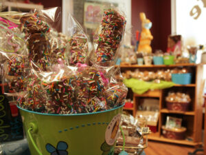 A bin of chocolates with sprinkles wrapped in clear plastic sits in the foreground, with a chocolate shop seen indistinctly in the background