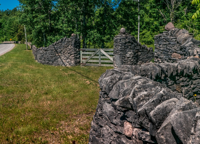 A photo taken along a dry stone wall with the gate visible in the midground