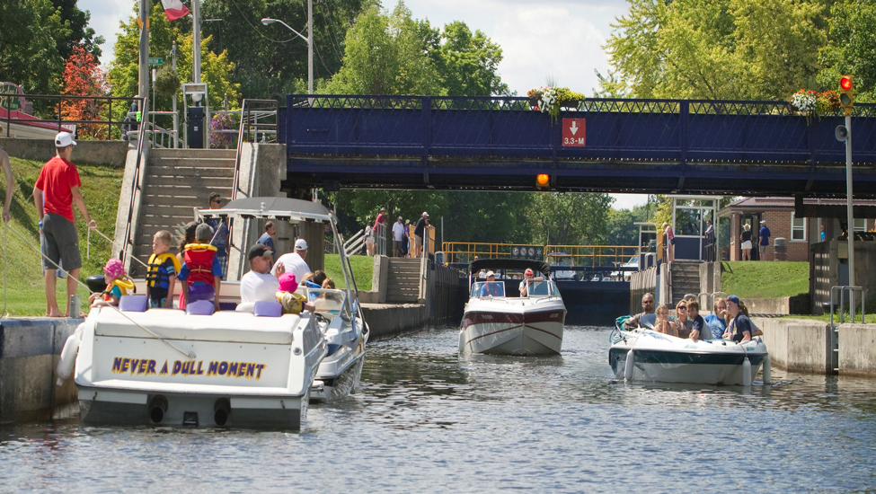 """Boats line up at the lock in Bobcaygeon, with one named """"Never a Dull Moment"""" seen prominently on the left"""