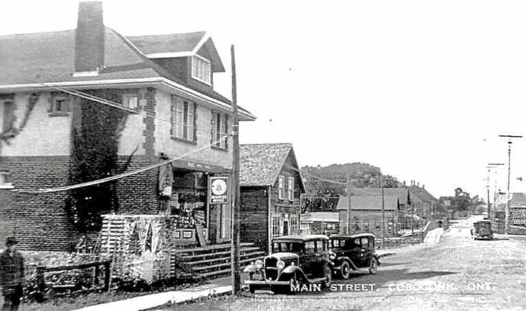 A black and white historical photo of Coboconk's main street, showing vintage cars parked outside a large building