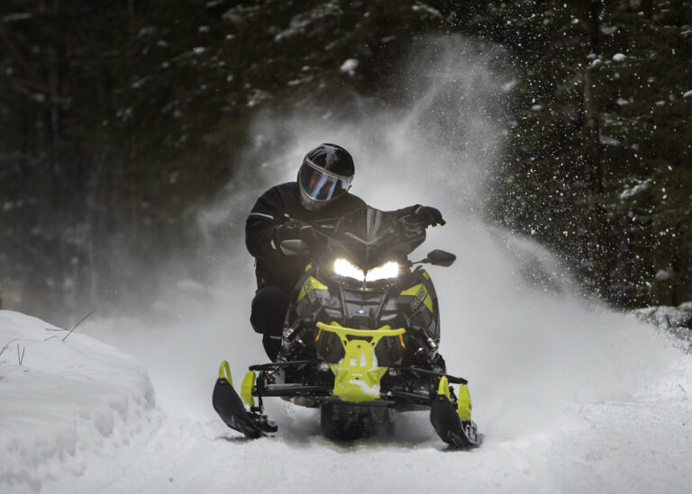 A snowmobiler takes a curve with a fine spray of snow flying out behind him