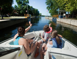 Three people in the bow of a boat wave to the operator as they navigate the lock in Bobcaygeon