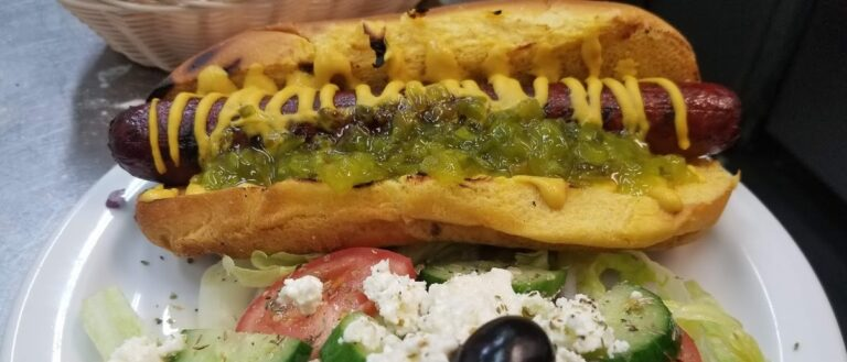 All-dressed hotdog on a plate with Greek salad from Sideways Bar & Grill in Campbellford
