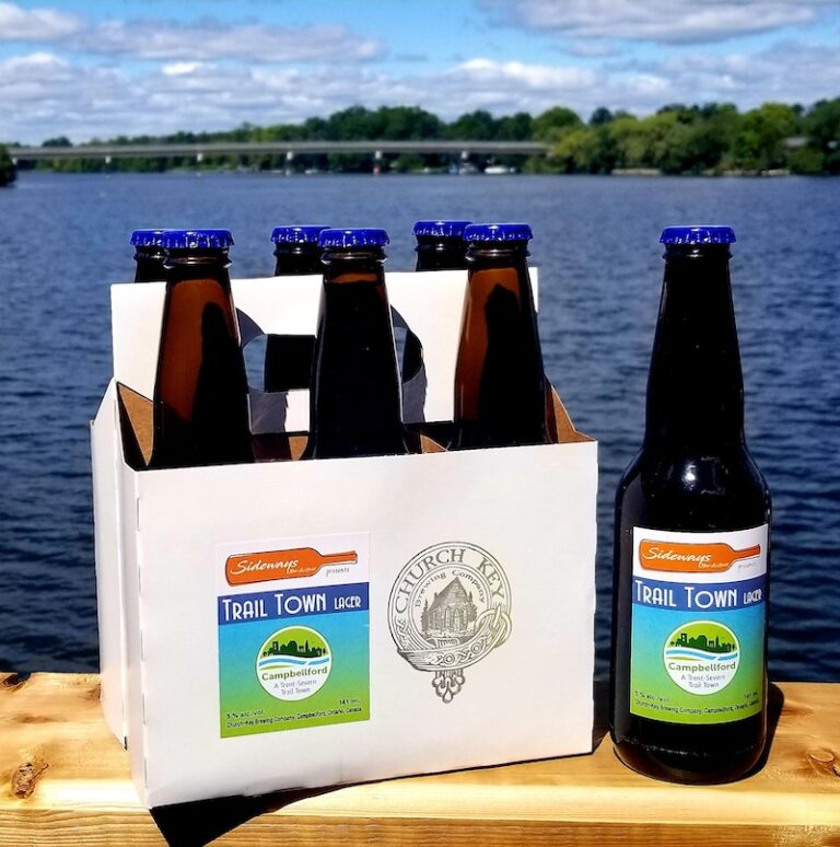 A six-pack of Campbellford Trail Town Lager sits beside the water, with an extra beer on the side to show the label