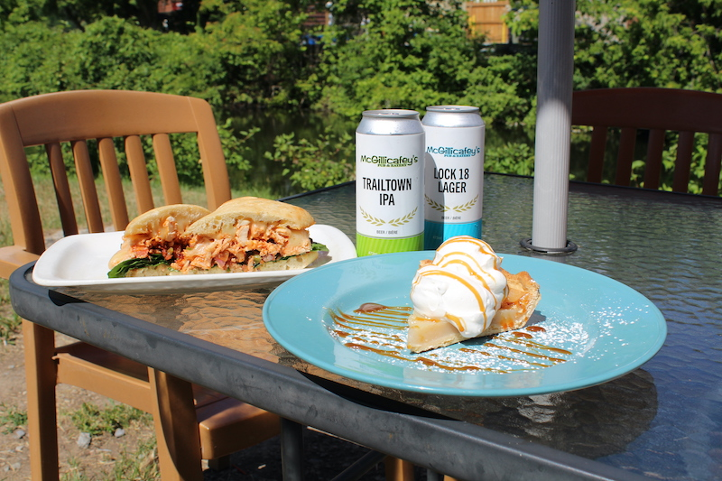 A trio of Taste of the TSW dishes on an outdoor table, including chicken foccaccia, two tall cans of beer, and a slice of water pie