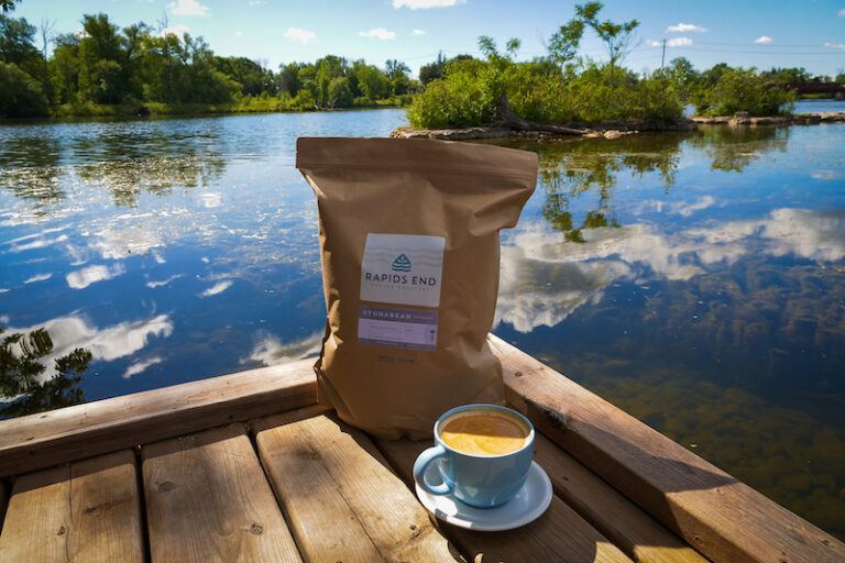 A bag of coffee beans an espresso sit on a wooden table overlooking the Ontonabee River