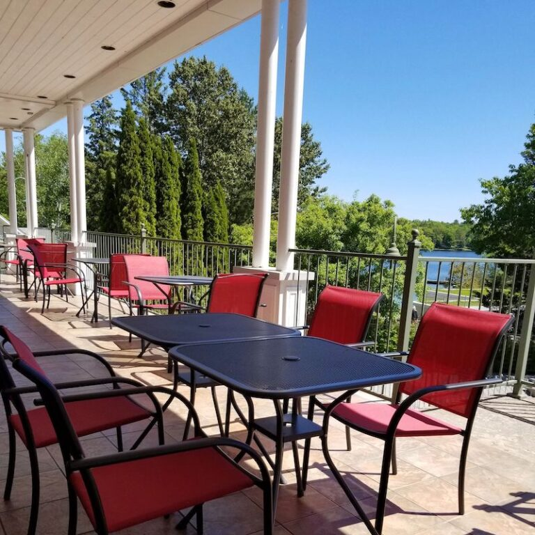 Porch at Burleigh Inn, lined with red chairs and patio tables
